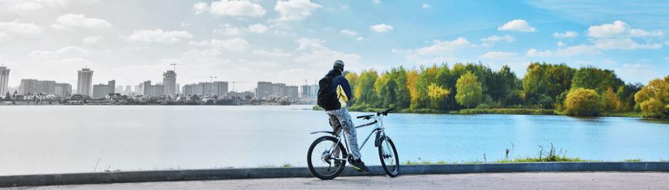 Homme à vélo entre ville et forêt